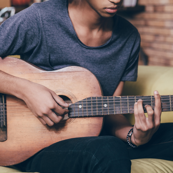 Young man from eastern Africa playing guitar
